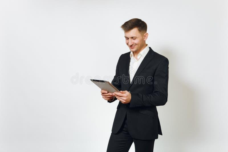 Hombre de negocios rico hermoso acertado joven en traje negro en el fondo blanco para hacer publicidad imagenes de archivo