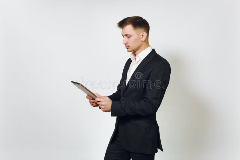 Hombre de negocios rico hermoso acertado joven en traje negro en el fondo blanco para hacer publicidad foto de archivo