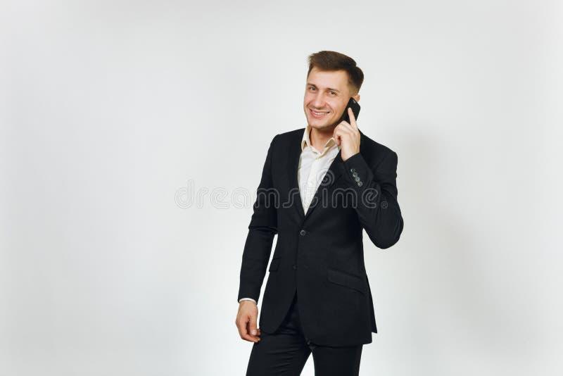 Hombre de negocios rico hermoso acertado joven en traje negro en el fondo blanco para hacer publicidad imágenes de archivo libres de regalías
