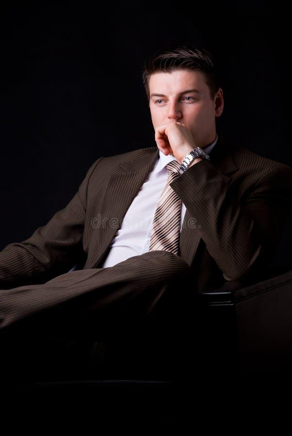 Hombre de negocios rico joven que se sienta en el sofá imagenes de archivo