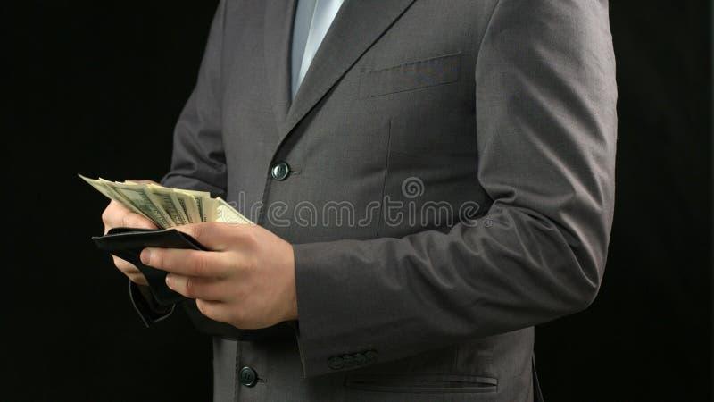 Hombre de negocios rico que cuenta los dólares en cartera, éxito financiero, ingresos personales fotos de archivo libres de regalías