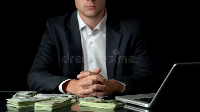 Hombre de negocios rico que se sienta delante del ordenador portátil, dinero en la tabla, inicio acertado imágenes de archivo libres de regalías