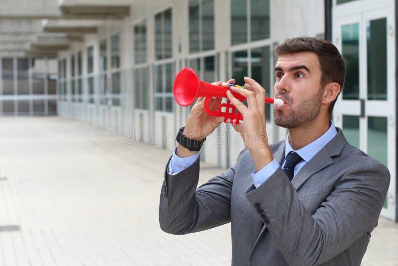 Hombre de negocios ruidoso que toca una trompeta plástica con el espacio para la copia fotografía de archivo libre de regalías