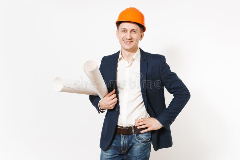 Hombre de negocios satisfecho joven en el traje oscuro, casco de protección anaranjado protector que lleva a cabo planes de los m imagen de archivo libre de regalías