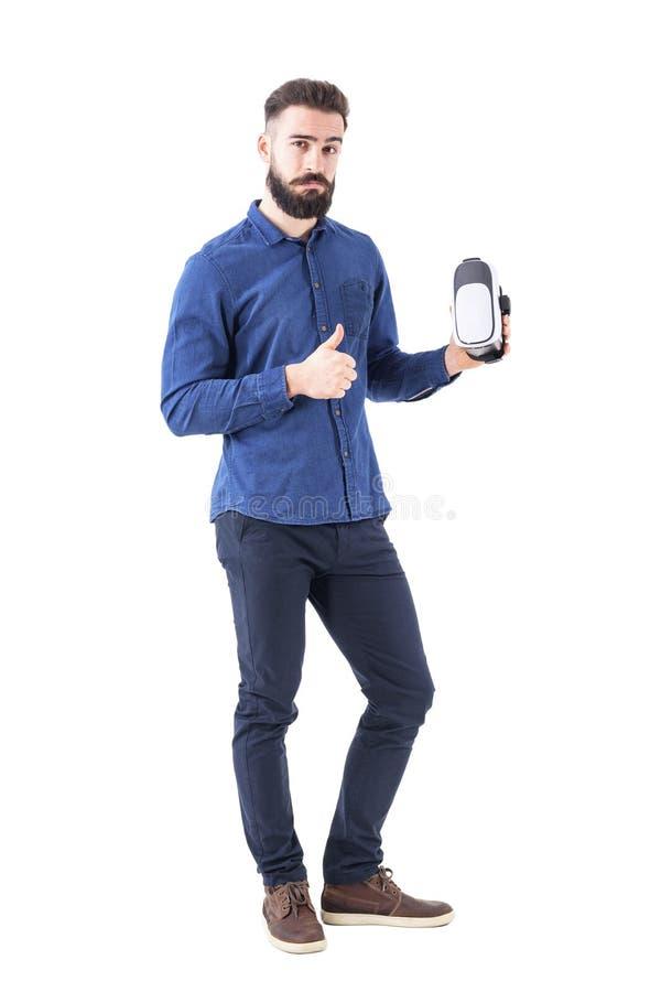 Hombre de negocios satisfecho que sostiene las auriculares del vr con el pulgar de la admiración encima del gesto que mira la cám fotos de archivo