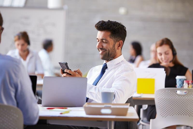 Hombre de negocios Sending Text Message en teléfono móvil en oficina fotos de archivo libres de regalías