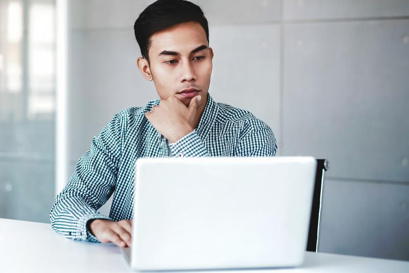 Hombre de negocios seriamente joven Working en el ordenador portátil del ordenador en oficina Mano en Shin, sentándose en el escr foto de archivo libre de regalías