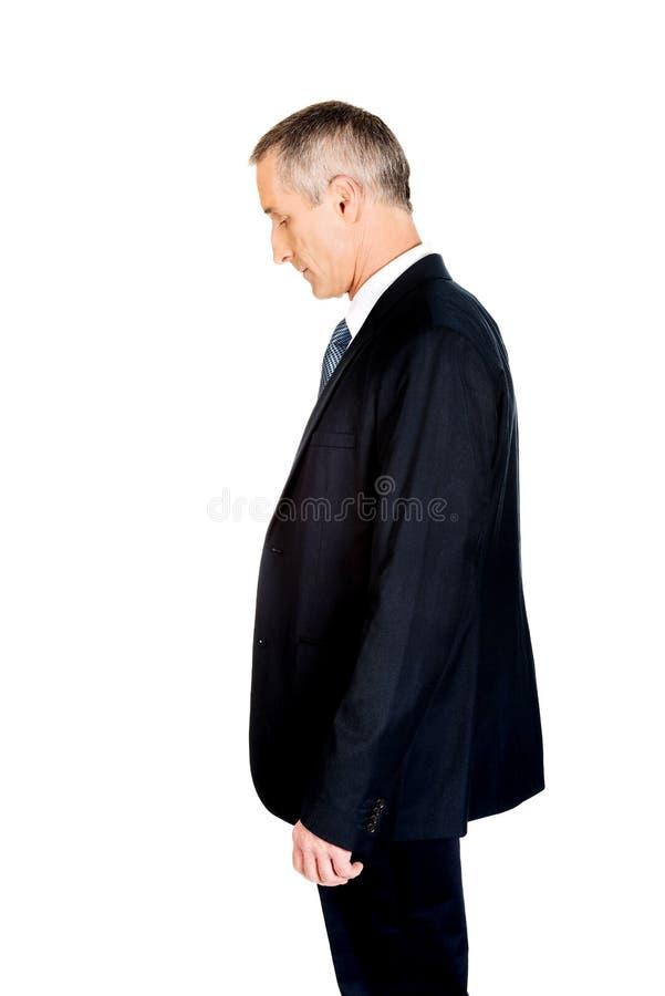 Hombre de negocios serio de la vista lateral que mira abajo fotografía de archivo