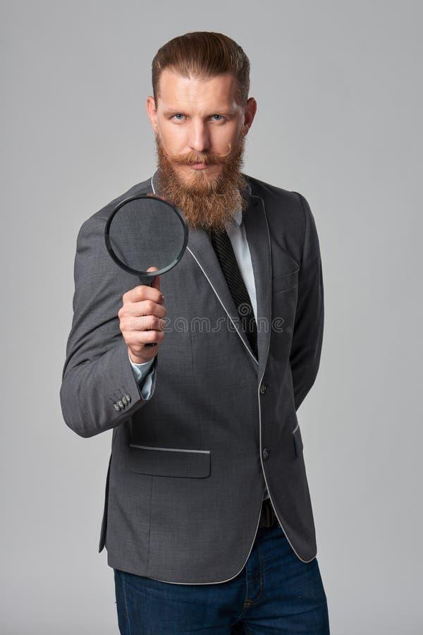 Hombre de negocios serio del inconformista con la lupa imagenes de archivo