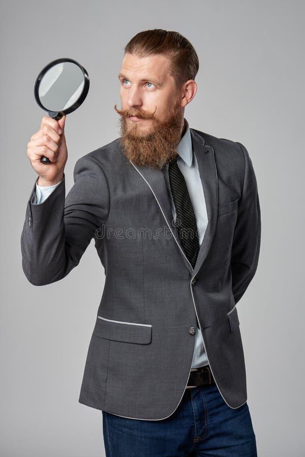 Hombre de negocios serio del inconformista con la lupa foto de archivo
