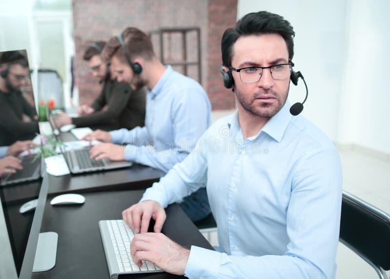 Hombre de negocios serio en auriculares que se sientan en un escritorio fotos de archivo