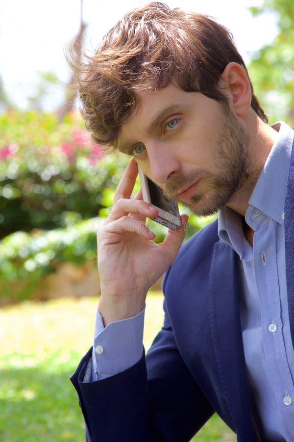Hombre de negocios serio en el teléfono mientras que trabaja con PC en primer del parque fotos de archivo