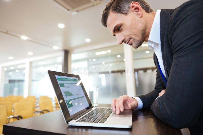 Hombre de negocios serio enfocado que trabaja con el ordenador portátil en sala de conferencias imagen de archivo