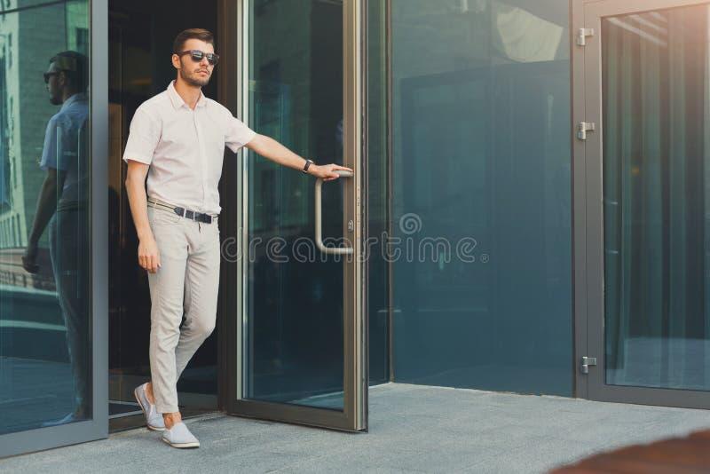 Hombre de negocios serio joven que deja el edificio imagen de archivo libre de regalías