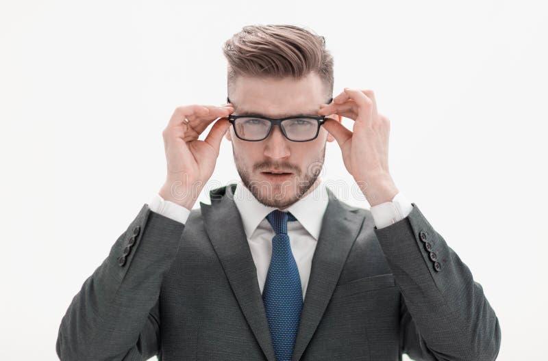 Hombre de negocios serio que ajusta sus vidrios foto de archivo