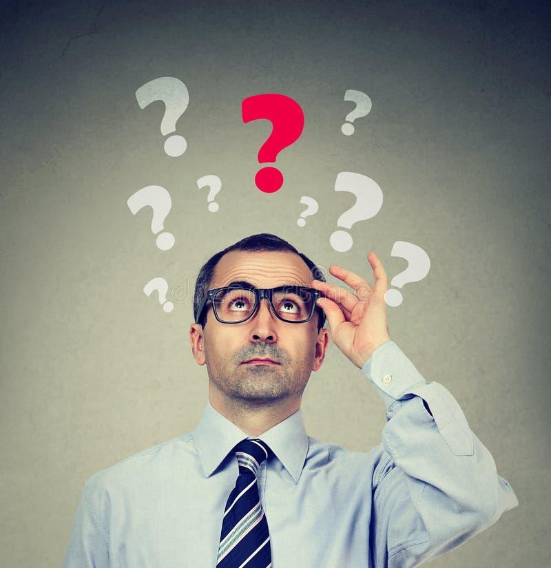 Hombre de negocios serio que considera para arriba una pregunta clave imágenes de archivo libres de regalías