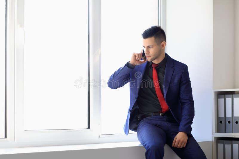 Hombre de negocios serio que habla en el teléfono celular que se sienta en travesaño de la ventana foto de archivo libre de regalías