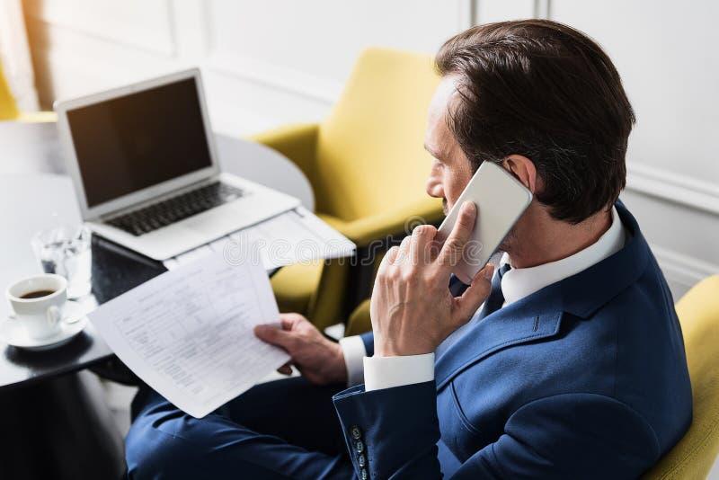 Hombre de negocios serio que habla por el teléfono en lugar de trabajo imagenes de archivo