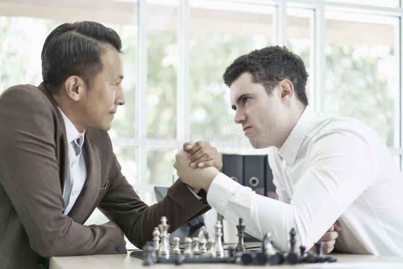 Hombre de negocios serio que juega al juego de ajedrez del tablero junto, ideas del éxito del planeamiento de la competencia y de foto de archivo