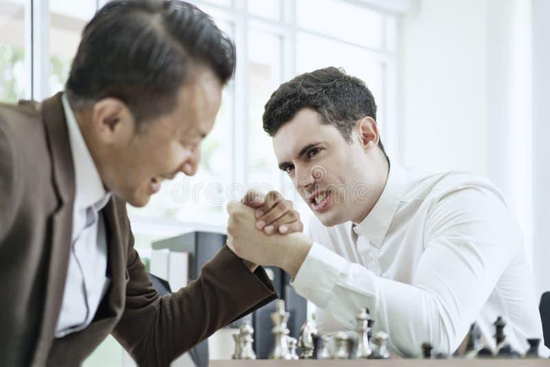 Hombre de negocios serio que juega al juego de ajedrez del tablero junto, ideas del ?xito del planeamiento de la competencia y de fotos de archivo libres de regalías