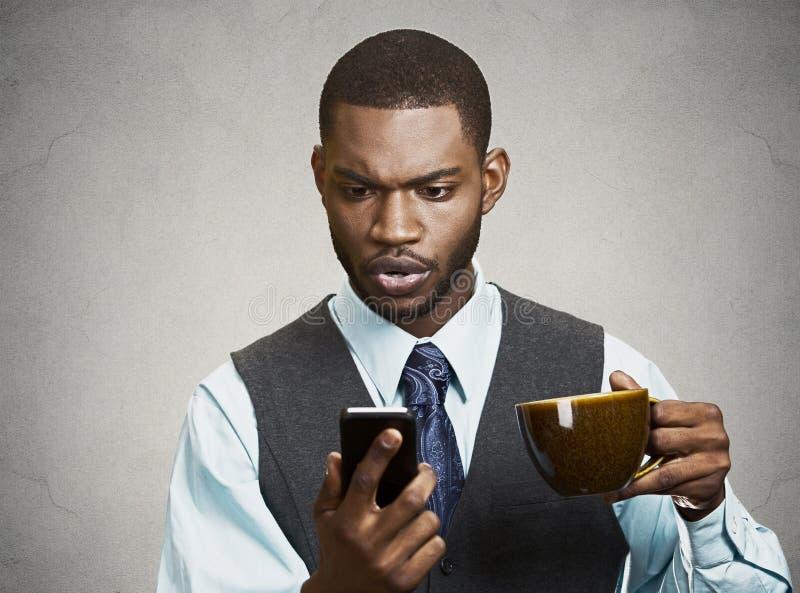 Hombre de negocios serio que manda un SMS en su teléfono imagen de archivo
