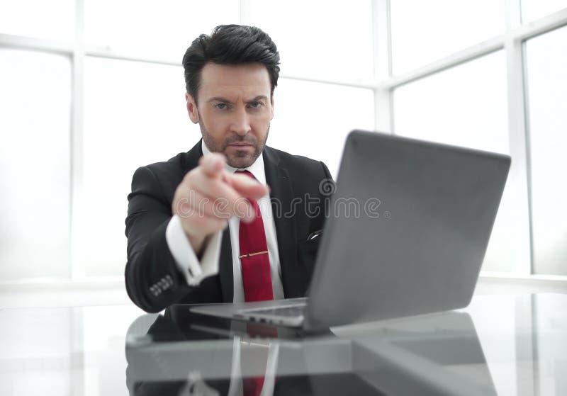 Hombre de negocios serio que señala el finger en usted, sentándose en su escritorio fotografía de archivo