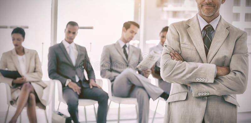 Hombre de negocios serio que se coloca delante de hombres de negocios fotografía de archivo