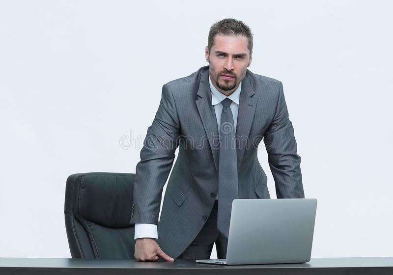 Hombre de negocios serio que se coloca detrás de un escritorio Aislado en blanco fotos de archivo libres de regalías