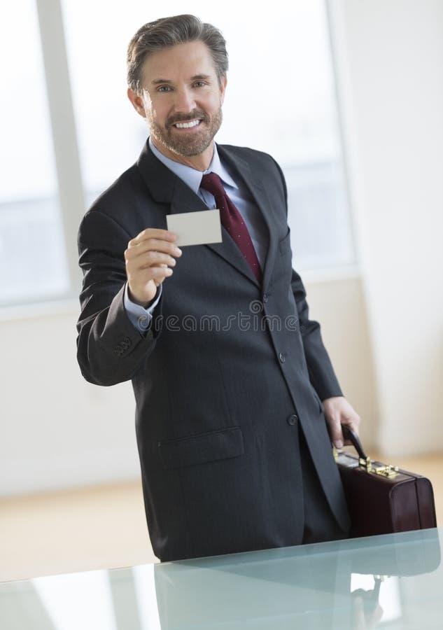 Hombre de negocios Showing Visiting Card en el escritorio imágenes de archivo libres de regalías