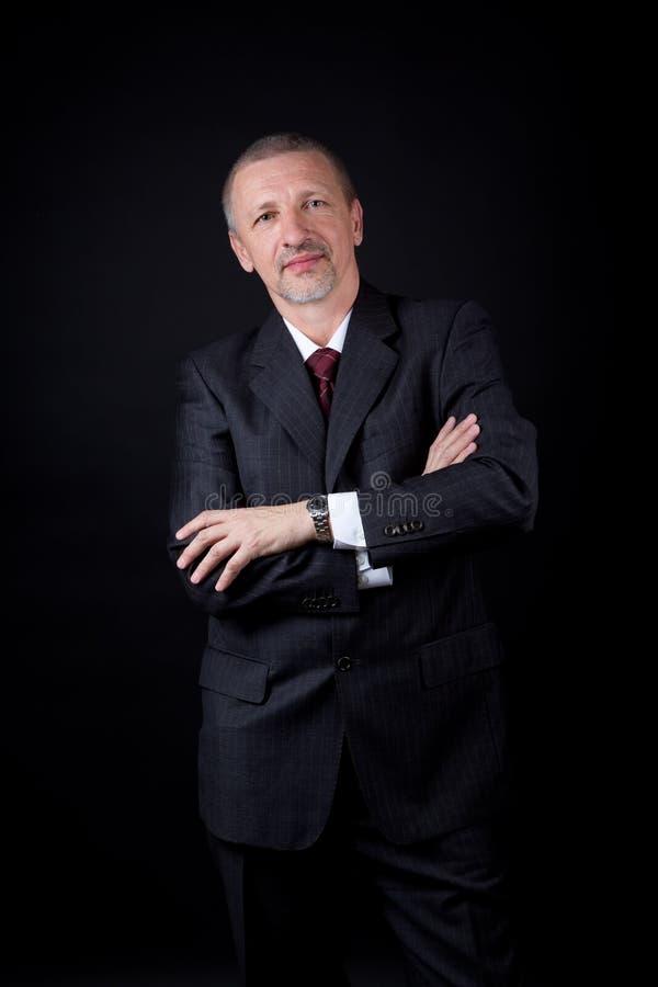 Hombre de negocios sin afeitar con los brazos cruzados imagen de archivo