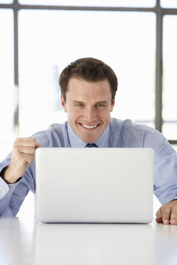 Hombre de negocios Sitting At Desk en oficina usando el ordenador portátil imagen de archivo