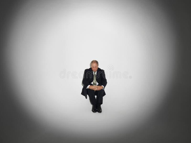 Hombre de negocios Sitting In Spotlight foto de archivo