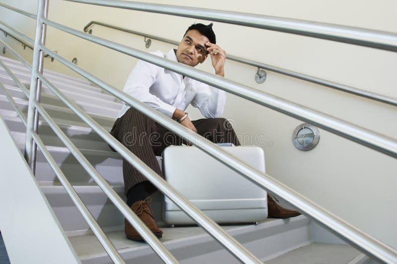 Hombre de negocios Sitting On una escalera imagenes de archivo