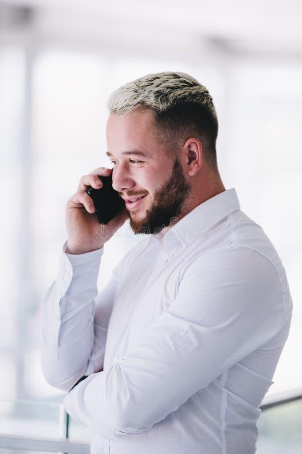 Hombre de negocios Smiles While Talking en el teléfono fotos de archivo libres de regalías