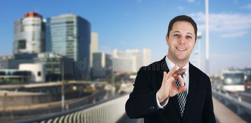 Hombre de negocios Smiling y sensación feliz dando la muestra de la autorización con la ciudad del negocio y edificios corporativ imagenes de archivo