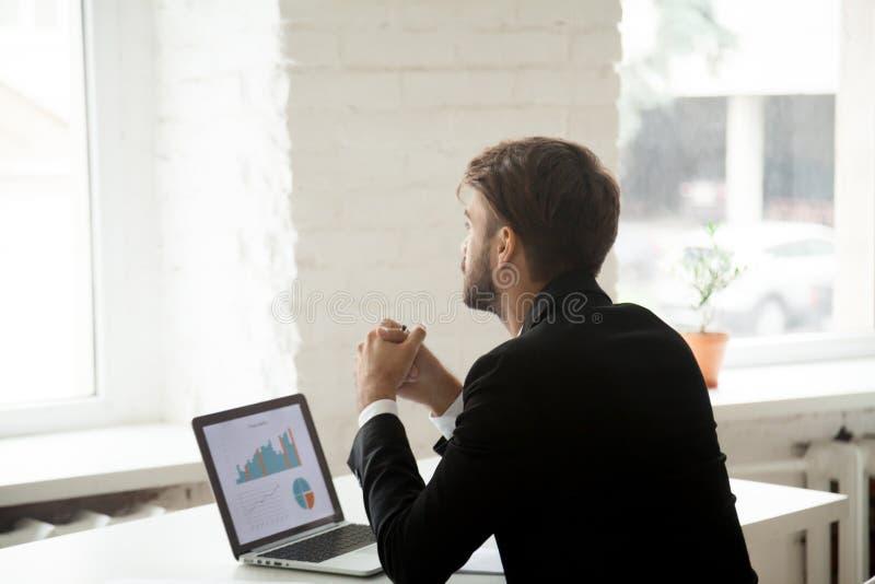 Hombre de negocios soñador que piensa en los proyectos futuros del negocio foto de archivo