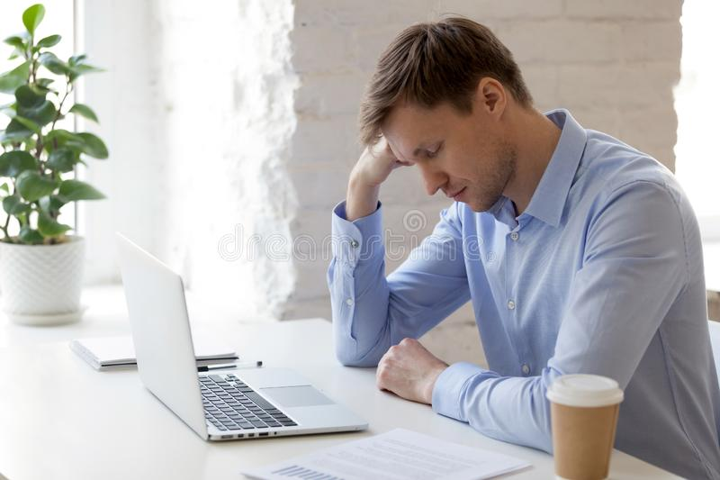Hombre de negocios soñoliento cansado que se sienta con los ojos cerrados en el lugar de trabajo fotos de archivo