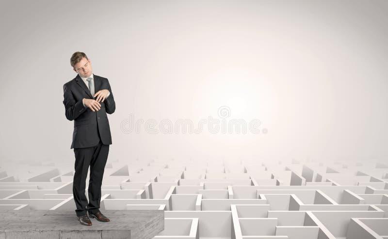 Hombre de negocios soñoliento en el top de un laberinto imagen de archivo