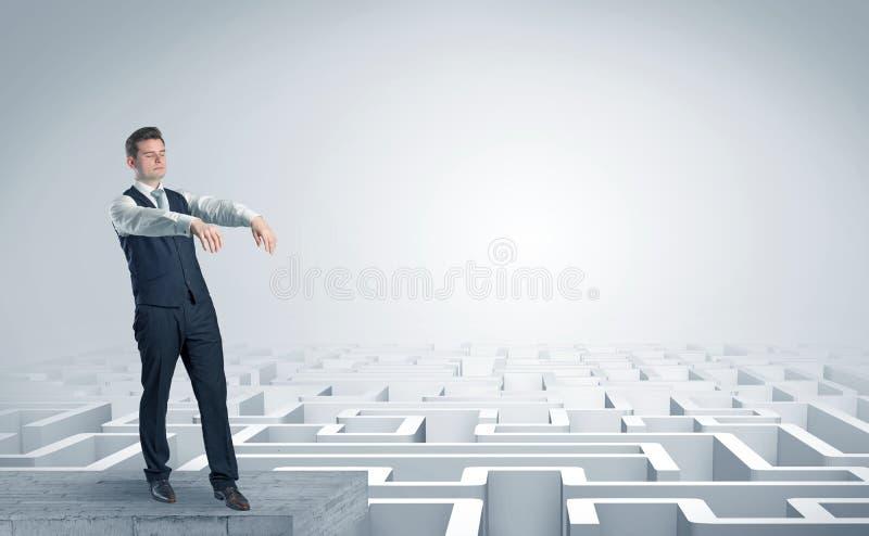 Hombre de negocios soñoliento en el top de un laberinto fotos de archivo