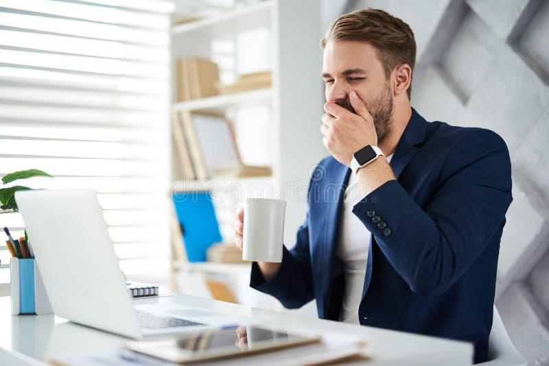Hombre de negocios soñoliento que trabaja en oficina imagen de archivo libre de regalías