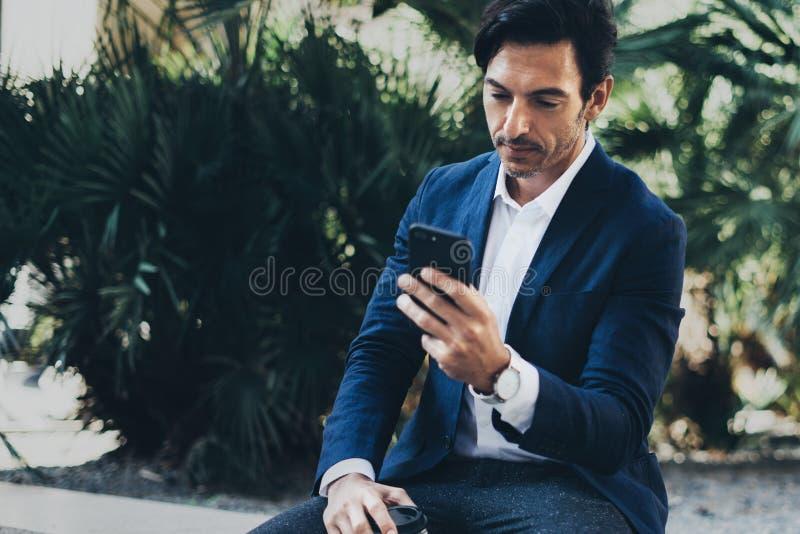 Hombre de negocios sonriente atractivo que hace la conversación video con los socios por el teléfono móvil Hombre que usa smartph fotos de archivo