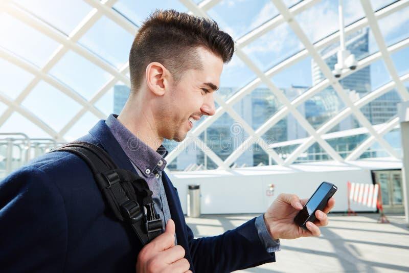 Hombre de negocios sonriente con el bolso y el teléfono celular imagen de archivo libre de regalías