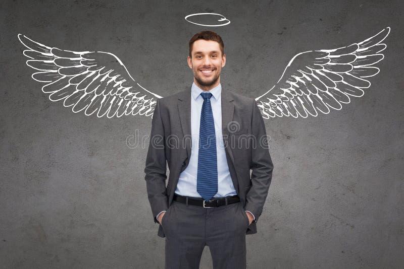 Hombre de negocios sonriente con las alas y nimbo del ángel fotografía de archivo