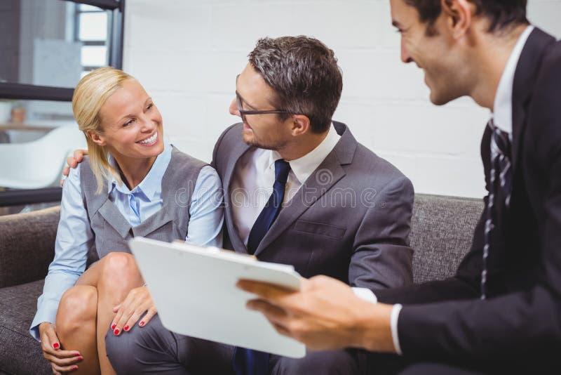 Hombre de negocios sonriente con los clientes que se sientan en el sofá foto de archivo libre de regalías
