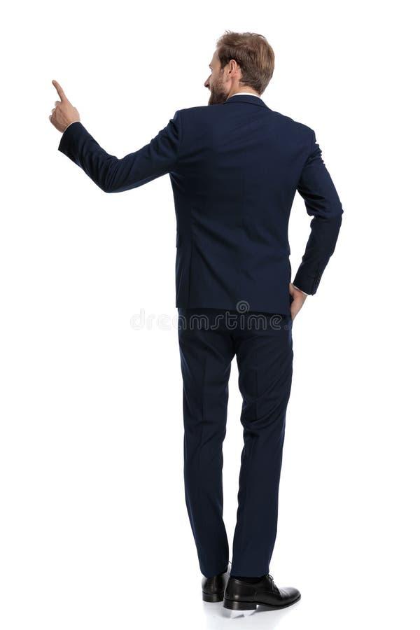 Hombre de negocios sonriente con traje azul marino que apunta de un lado a otro imágenes de archivo libres de regalías