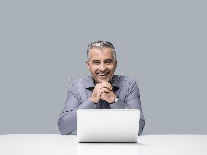 Hombre de negocios sonriente confiado en la oficina fotos de archivo