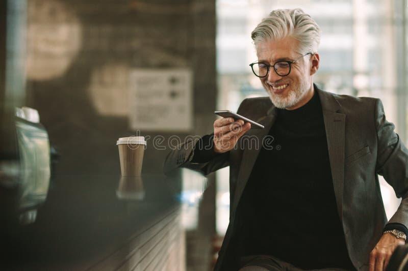 Hombre de negocios sonriente en el café que hace llamada de teléfono imagen de archivo libre de regalías
