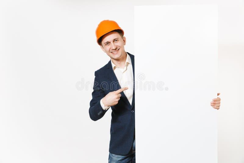 Hombre de negocios sonriente en el traje oscuro, el casco de protección protector llevando a cabo el material en blanco vacío bla foto de archivo libre de regalías