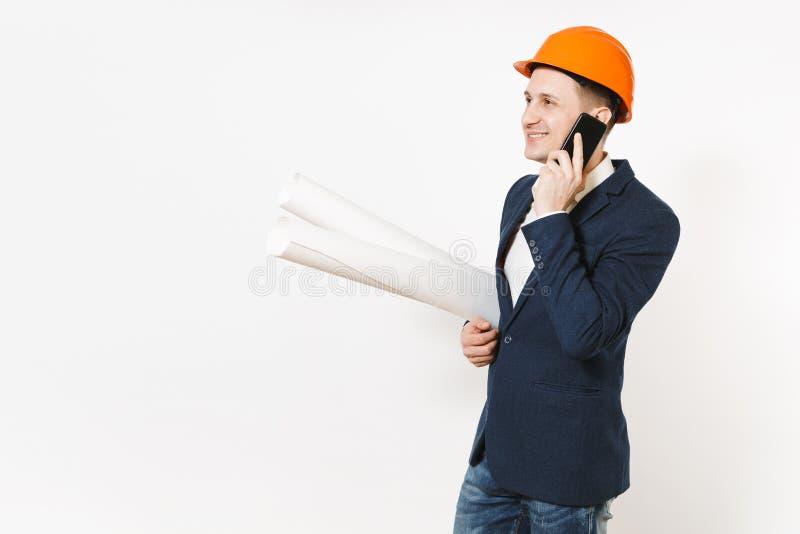 Hombre de negocios sonriente en el traje oscuro, casco de protección protector que lleva a cabo planes de los modelos, hablando e fotografía de archivo libre de regalías