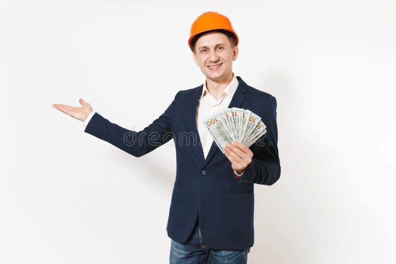 Hombre de negocios sonriente en el traje oscuro, paquete anaranjado protector de la tenencia del casco de protección de dólares,  imágenes de archivo libres de regalías
